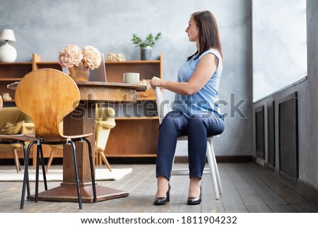 Photo of  Beautiful female office worker in yoga pose Ardha Matsyendrasana or Half Lord of the Fishes, Half Spinal Twist Pose, Vakrasana sitting on chair
