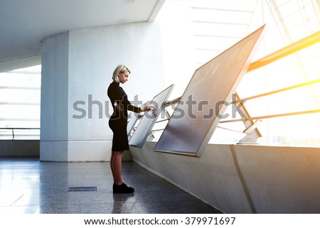 Beautiful female reading advertising about a project on interactive computer display while standing in office interior, businesswoman searching information on high tech modern device  #379971697