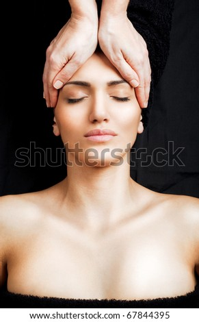 Beautiful female receiving relaxing facial massage at spa, eyes closed