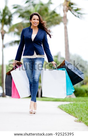 Beautiful female shopper with bags walking outdoors