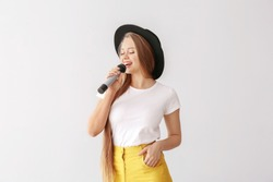 Beautiful female singer with microphone on light background