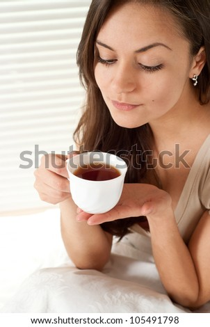Beautiful female sitting on a bed with a cup on a light background