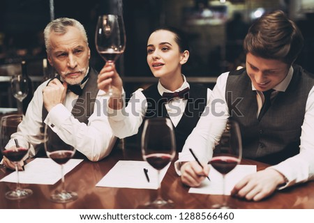 Beautiful female sommelier is holding glass of wine and tasting sediments. Confident sommelier tasting wine in restaurant Stock photo ©
