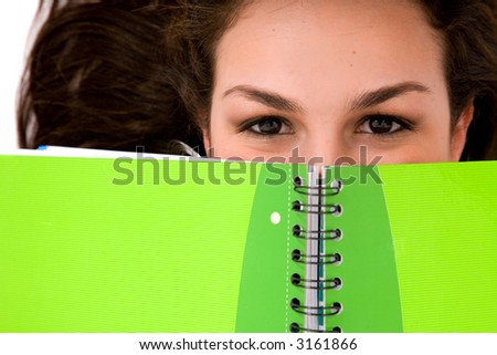 beautiful female student peeping over a green notebook while lying on the floor on a white background