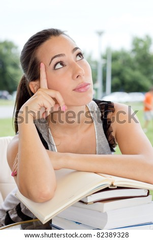 Beautiful female student sitting in the  restaurante with books and daydreaming.