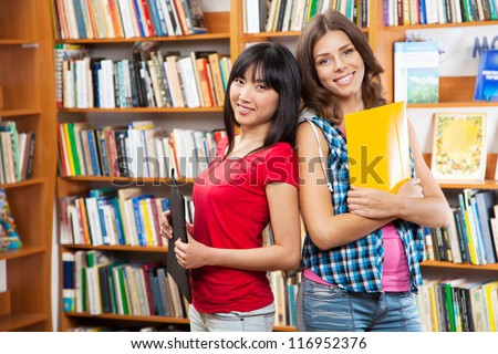 Beautiful female students in a university library - stock photo