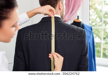 Beautiful female tailor is standing near her male client. She is measuring back of a man. The woman is looking at the tape-measure with concentration