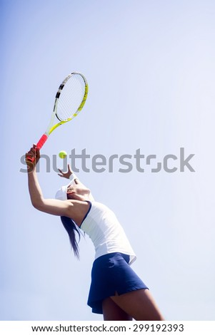 Beautiful female tennis player serving outdoor