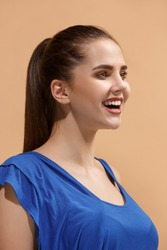 Beautiful female three-quarters portrait. isolated on pastel studio backgroud. The young emotional happy woman standing.The human emotions, facial expression concept. Profile view. Trendy colors