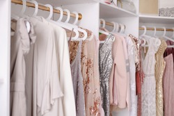Beautiful female wardrobe. A lot of party dresses hanging on hangers in closet. Vintage clothing rental concept. Women's space. Large selection of various clothes. Small boutique showroom fashion shop