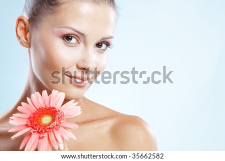 Beautiful female with fresh makeup and clear skin holding pink daisy over blue studio shot - stock photo