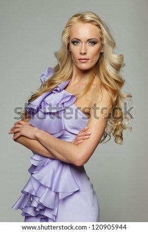 Beautiful female with long blond hair standing with folded hands, over gray background