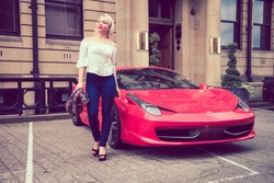 Beautiful female woman with blonde hair, and red lipstick, walking with attitude from a beautiful red coloured sports car.