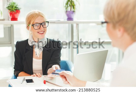 Beautiful female worker issuing credit card to a customer