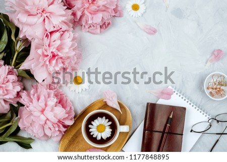 Beautiful feminine flat lay mockup with pink peonies, various stationery and glasses on grey background