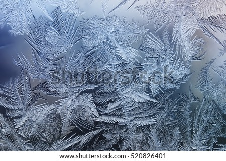 Stock Photo beautiful festive frosty pattern with white snowflakes on a blue background on glass