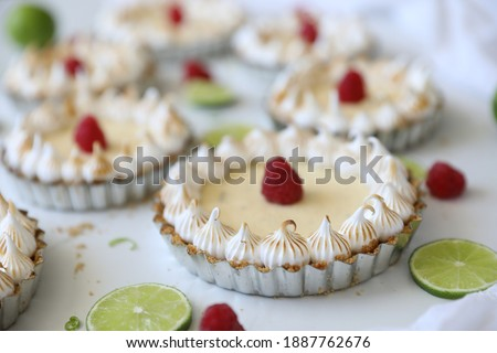 Beautiful festive key lime mini tartlets with meringue and raspberries, traditional American dessert made of lime juice, egg yolks and sweetened condensed milk. Citrus fruit dessert for the Holidays