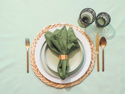 Beautiful festive table setting in green colors for St.Patrick's day with golden cutlery. Top view of Saint Patrick's day holiday table with green linen tablecloth and napkin, green glasses. Flat lay