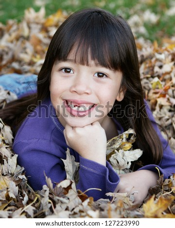 Beautiful Filipino Girl Smiling in a Fall/Autumn setting Showing Missing Top Tooth