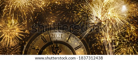 beautiful fireworks explosion for new years eve 2021 celebration, golden rockets at countdown clock at midnight with light effects