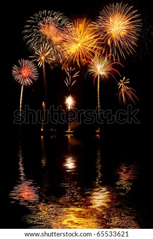 Beautiful fireworks on black sky with reflections in lake