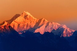 Beautiful first light from sunrise on Mount Kanchenjunga, Himalayan mountain range, Sikkim, India. Orange tint on the mountains at dawn