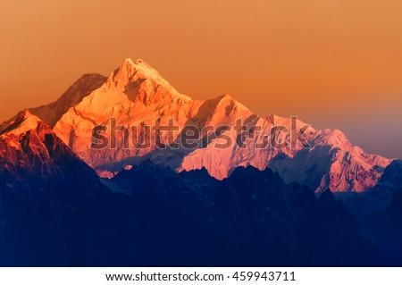 Stock Photo Beautiful first light from sunrise on Mount Kanchenjunga, Himalayan mountain range, Sikkim, India. Orange tint on the mountains at dawn