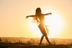 Beautiful fit girl body silhouette dancing at sun light at horizon in transparent cloth, activity outdoors