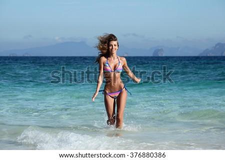 Beautiful fit woman in bikni run on tropical beach