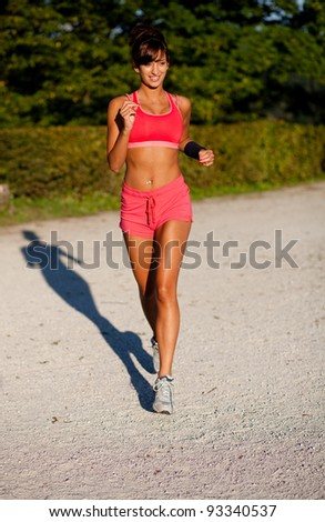 Beautiful fit young woman jogging in a park