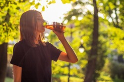 Beautiful fitness athlete woman are drinking iced tea after workout exercising on sunset evening in park. Outdoor portrait with sun glares.