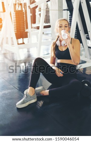 Beautiful fitness athlete woman drinking water after work out exercising in modern gym. Sport, healthy lifestyle concept. Photo stock ©