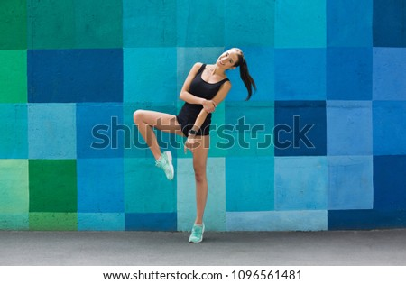 Beautiful fitness girl posing on blue wall background outdoors, copy space. Sporty woman with perfect body, healthy lifestyle and bodycare concept #1096561481