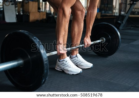 Beautiful fitness man with weights doing exercises. pulling the barbell from the floor #508519678