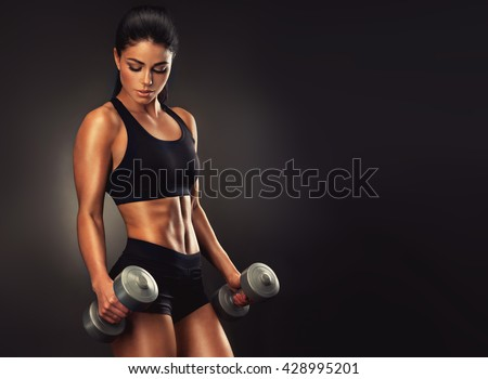 Beautiful fitness woman lifting dumbbells . Fitness sporty woman showing her well trained body . A beautiful girl\'s body with rippling muscles from strength training .