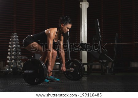 Beautiful Fitness Woman preparing to lift some heavy weights