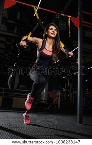 Beautiful fitness woman training with trx fitness straps. Suspension exercising in gym Stock foto ©