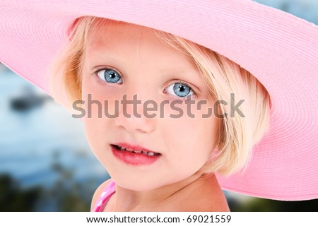 Beautiful five year old girl in big pink summer hat and blue eyes outside.