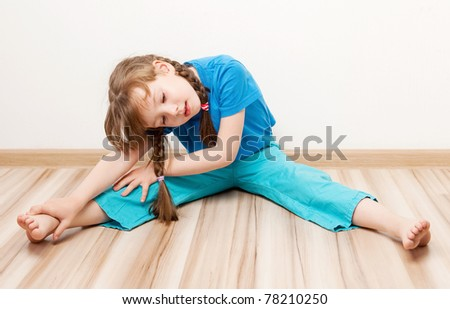 beautiful five year old girl stretching the muscles of her back and legs  at home