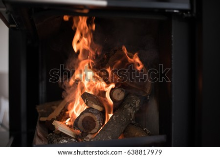 Beautiful flame fireplace. Wood burning bright flames in a modern fireplace with glass door #638817979