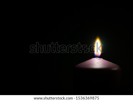 Beautiful flame on purple candle in the dark. Copyspace for text