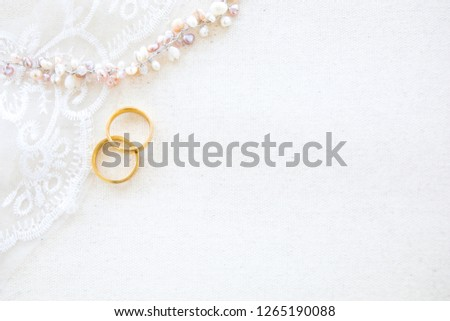 beautiful flat lay canvas background with a pair of gold rings and pearl necklace for wedding or engagement decorated with white lace, gift box and flower bouquet with copy space