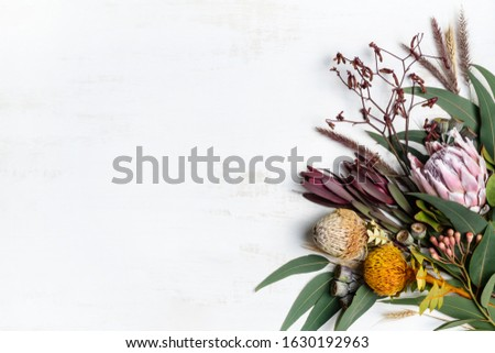 Beautiful flat lay floral arrangement of mostly Australian native flowers, including protea, banksia, kangaroo paw, eucalyptus leaves and gum nuts on a rustic white background.