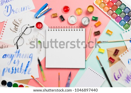 Beautiful flatlay arrangement with watercolors, brushes, brushpen, paint with notebook with blank copyspace page and other stationery and art supplies Lettering practice. Creativity, education concept