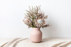 Beautiful floral arrangement including beautiful dried pink King Proteas and delicate thryptomene flowers, in a stylish pink vase.