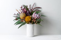 Beautiful floral arrangement of mostly Australian native flowers, including protea, banksia, kangaroo paw eucalyptus leaves and gum nuts, in a white vase on a white table with a white background.