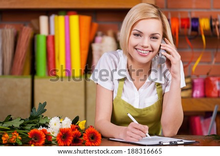 Beautiful florist at work. Beautiful young female florist writing something at note pad and taking on the phone while standing at her working place