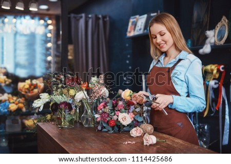 Beautiful florist with bouquet at the counter