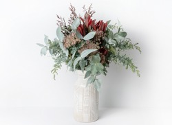 Beautiful flower arrangement of mostly Australian native flowers, including Silvan Reds, Queen Anne's Lace, Wattle foliage and Eucalyptus leaves, in a ceramic white vase, with a white background.