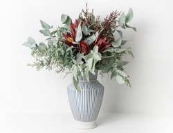 Beautiful flower arrangement of mostly Australian native flowers, including, Silvan Reds, Wattle foliage and Eucalyptus leaves, in a white and blue strip vase, with a white background.